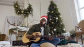latin american : Happy african guy with guitar and bengal light sittingon the floor in a glittering golden confetti on the background of a Christmas tree and christmas decorations