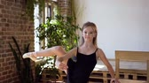 sukénka : Charming girl in black tutu performs element of classical ballet exercise at the ballroom. A young beautiful ballerina in black tutu doing stretching and warm-up exercises