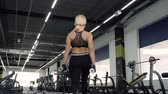 blondehair : Woman making steps with dumbbells during the training in the gym.