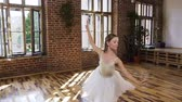 színházi próba : Graceful charming ballerina in white tutu perform classical dance at ballet school. Young slim ballerina in white dress performs ballet dance in the Studio