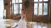 klapki : Ballet dancer dressed in white tutu perform classic ballet dance, she trains gracefully in pointe ballet shoes in ball school. Graceful charming ballerina practicing ballet movements at the dance-hall Wideo