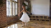 children ballet : Young ballerina performs a classical ballet in pointe shoes and tutu on the background of a large window and red brick wall. Elegant ballerina dancing in pointe shoes and in a white fluttering dress at moder dancing-hall