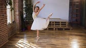 klapki : Graceful dance ballerina practicing exercise classical ballet in sport school. Flexibility exercise training. Young ballerina in white tutu dress doing stretching splits of classical ballet