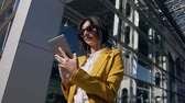 beyaz yaka : Portrait of businesswoman in suit holding in hand and uses tablet. Young woman using tablet computer touchscreen outdoor, on modern office glass building background Stok Video