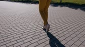 nőiesség : Young businesswoman in suit and shoes with heels goes to the city. Close-up of female slim feet walking through the downtown