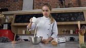 sideview : Young female confectioner pouring white egg cream in bowl for mking sour cream.