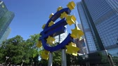 kapitalizmus : Frankfurt, Germany. July 2019. The Symbol of the Euro monument in front of the Eurotower