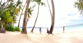 calm : tourists walk on sandy beach among palmtrees in tropical resort island. Popular travel destination in Asia