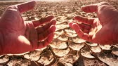 Farmers hands split piece of dry soil from field affected by drought. Slow motion video of deserted cracked barren soil