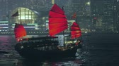 Виктория : Traditional wooden junk boat in Victoria harbor at night making short tourist trips giving opportunity for beautiful panoramic views of modern architecture of Hongkong Стоковые видеозаписи