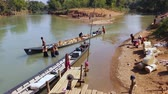 travel : citizens of traditional Burmese village near Inle lake follow their simple lifestyle by transporting goods and bathing on the river bank. Popular sight Stock Footage