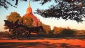 travel : travelers and local Burmese people riding horse cart near Htilominlo Buddhist Temple at sunset time. Historical area includes hundreds of ancient temples