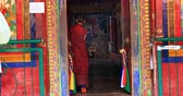sagrado : Ancient Buddhist monastery Lamayuru of Bon Buddhism scene. Young monk enters inside gompa through decorated door way