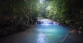 平和 : Waterfall hidden in jungle forest. Emerald pool with transparent water under foliage of dense trees vegetation