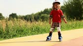 patim : Little boy, three years old, scatting downhill, smiling and speeding up