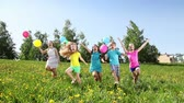 Group of happy kids, boys and girls running with balloons in the field on sunny summer day Stock Footage