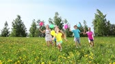 run : Group of boys and girls running in the spring dandelion field on sunny day with balloons