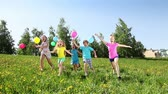 gritando : Group of happy kids run with balloons having happy party in the spring sunny day on dandelion filed Stock Footage
