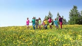 group : Large group of diverse looking children boys and girls running in dandelion yellow field on spring sunny day view from the side