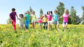 Large group of diverse looking kids boys and girls running in dandelion yellow field on spring sunny day Stock Footage