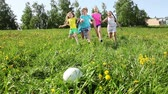 Group of kids, boys and girls run to take the ball first on spring grass with dandelion field happy and laughing