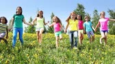 group : Large group of kids run in dandelion field holding hands at sunny spring day