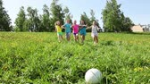 Group of happy kids, boy and girls run to take the ball first on spring grass with dandelion field happy and laughing
