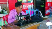 noivo : BANGKOK THAILAND FEB 26 2015: Tailor works on a city street. Many Thai people are engaged in small businesses in Bangkok and other places Stock Footage