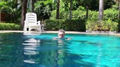 anos : An older spa Visitor swimming in a swimming pool on holiday