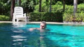 manmetro : Happy older man swimming in a small swimming pool