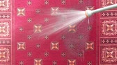 koberec : Red rug is washed with a spray of water