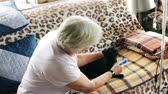 Elderly woman takes care of a cat, combing her wool