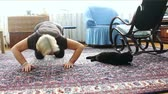 An elderly woman exercising with a cat Stock Footage