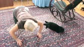 An elderly woman doing exercises, cat lies next to her