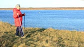 Elderly woman on the river bank. Nordic walking