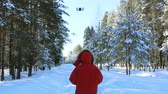Young man and flying drone in winter forest above the road