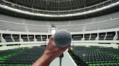 mikrofon : Shot of a hand holding a microphone during rehearsal and sound-check before a show at the venue.  There is no audience so you see empty seats and the lights are turned on.