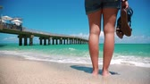 step by step video : Beautiful tilt up of woman standing in front of ocean and pier at beach in Miami-Sunny Isles