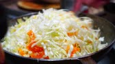 finely : Woman cooks braised cabbage and carrots in the pan