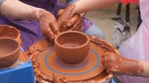 loam : Hands of potter teaches the child how to make pots. Concept - transfer of experience,