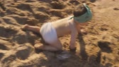 A little boy is playing on the sand on the beach. A baby crawls and laughs studying all around. 動画素材