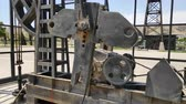 Oil pumps working on a field. Metal oil derricks work, pumping oil, close up. 動画素材