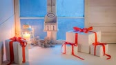 prezent : Christmas gifts moving on white table by blue frozen window Wideo