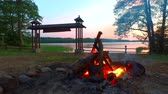 огонь : Bonfire at sunset by the lake in summer