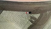 сельскохозяйственный : Red tractor working on spring spring field, Poland, aerial view