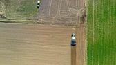 сельскохозяйственный : Aerial view of green tractor plowing a spring field, Poland