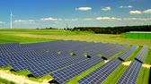 Aerial view of solar panels, wind turbines, green field and blue sky, Poland Stock Footage