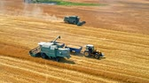 farming machinery : Aerial view of combine drop the grain onto tractor trailer