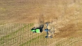 Green tractor plowing field on autumn, view from drone