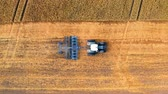Aerial view of blue tractor plowing field after harvest